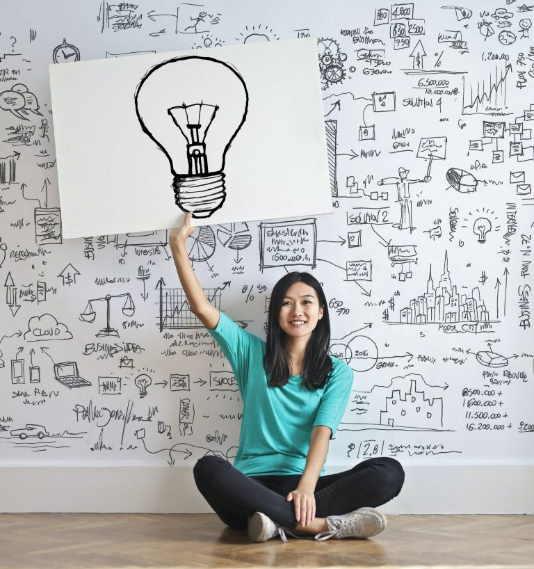 A Woman Displaying a Drawing with A Light Bulb